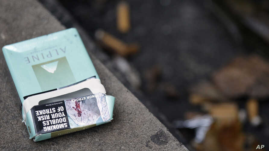 An empty cigaret packet sporting graphic health pictures lies on the ground outside a local pub in Sydney, Australia,July 6, 2011.