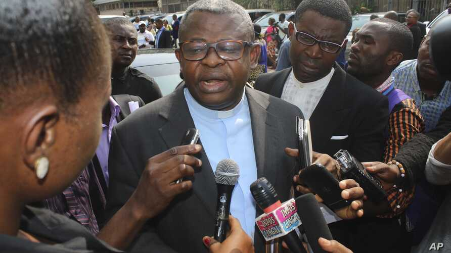 FILE - Priest Donatien Nshole, First Deputy Secretary-General of the National Episcopal Commission, speaks to journalists after a meeting in Kinshasa, Democratic Republic of Congo, Wednesday, Dec. 21, 2016. Mediators urged Congo's president and oppos