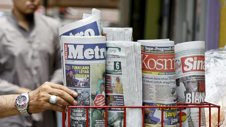 A man takes a copy of newspaper at a grocery shop in Shah Alam, Malaysia, Monday, March 26, 2018. Malaysia's government on Monday proposed new legislation to outlaw fake news with a 10-year jail term for offenders, in a move slammed by critics as a d