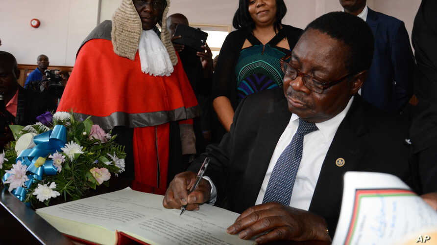 FILE - Newly elected Malawian president Peter Mutharika signs the oath book after he was sworn in, at the High Court in Blantyre, Malawi, May 31, 2014.