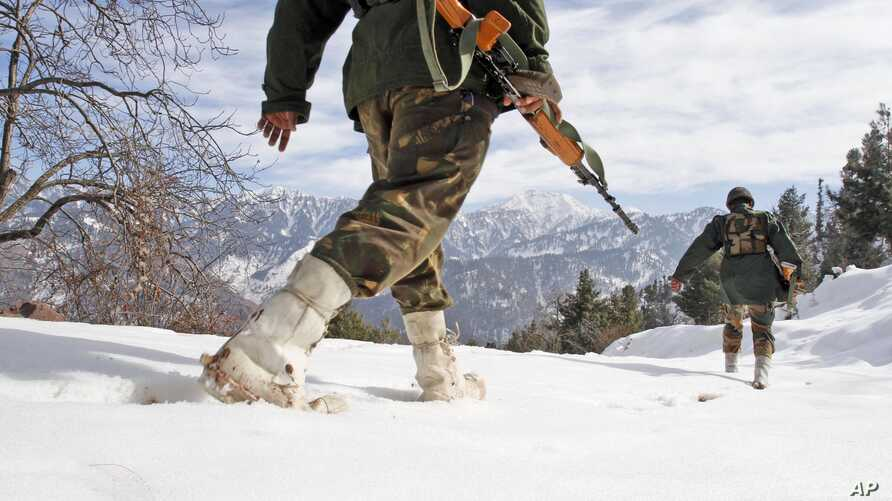 Indian army soldiers patrol near the Line of Control (LOC), the line that divides Kashmir between India and Pakistan, in Churunda village, about 150 Kilometers (94 miles) northwest of Srinagar, India, Jan. 15, 2013.