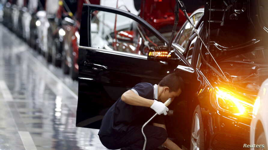 An employee works on an assembly line producing Mercedes-Benz cars at a factory of Beijing Benz Automotive Co. (BBAC) in Beijing, Aug. 31, 2015.