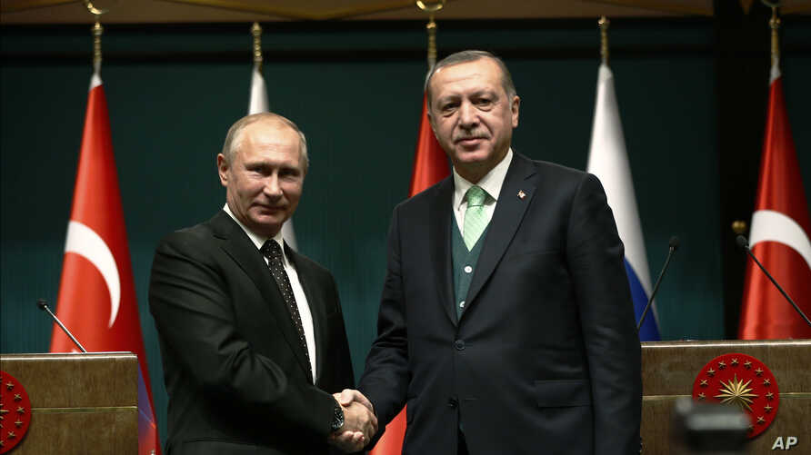 Turkey's President Recep Tayyip Erdogan, right, shakes hands with Russia's President Vladimir Putin, left, following their joint news statement after their meeting at the Presidential Palace in Ankara, Dec. 11, 2017.