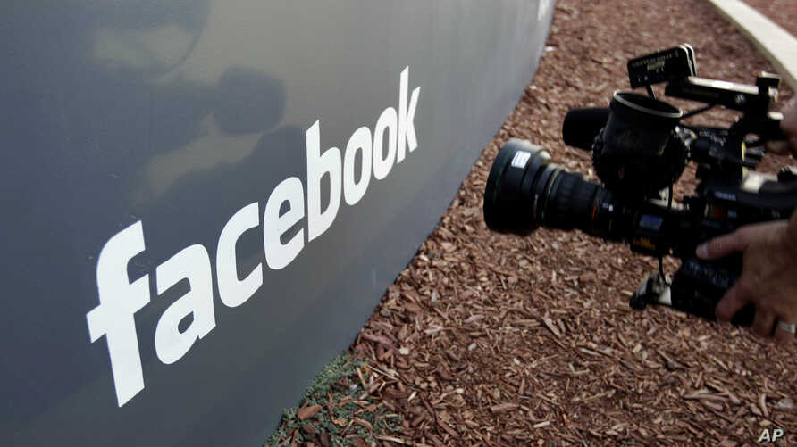FILE - A television photographer shoots the sign outside of Facebook headquarters in Menlo Park, Calif., May 18, 2012.
