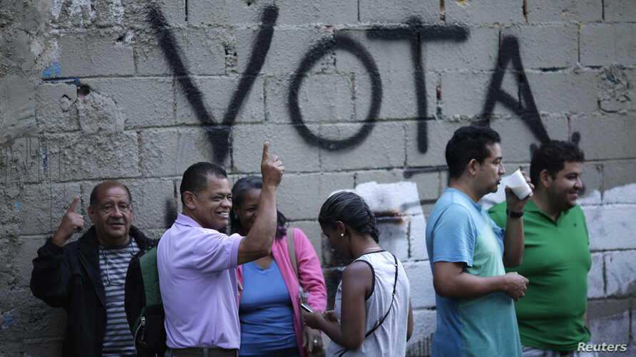 """People wait in line next to the word """"Vote"""" spray painted on a wall before voting during the Constituent Assembly election in Caracas, Venezuela, July 30, 2017."""