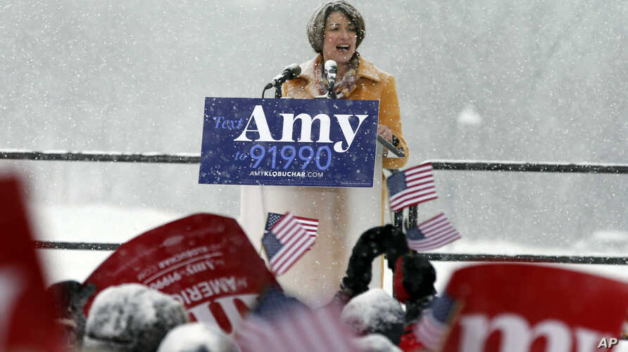 Democratic Sen. Amy Klobuchar, left, addresses a snowy rally where she announced she is entering the race for president, Feb. 10, 2019, at Boom Island Park, in Minneapolis, Minnesota.