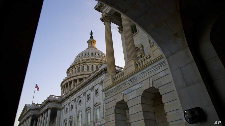 The sun begins to set against the Capitol dome as the budget battle continues, Sept. 30, 2013 in Washington.