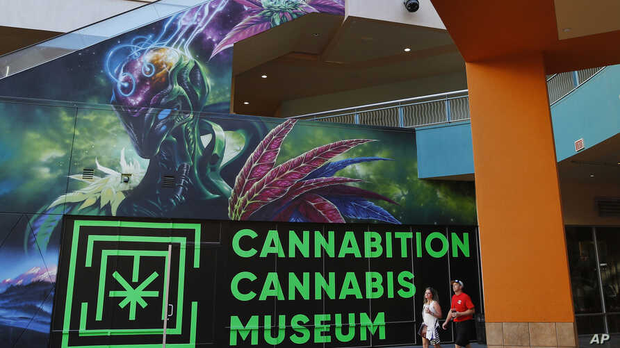 FILE - In this Tuesday, Sept. 18, 2018, file photo, people walk by the Cannabition cannabis museum in Las Vegas. The legal marijuana industry exploded in 2018, pushing its way further into the cultural and financial mainstream in the U.S. and beyond.