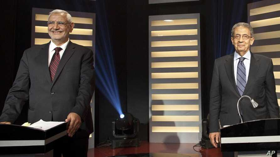 Egyptian presidential hopefuls Amr Moussa (R) and Abdel-Moneim Abolfotoh smile during a televised debate in Cairo May 10, 2012.