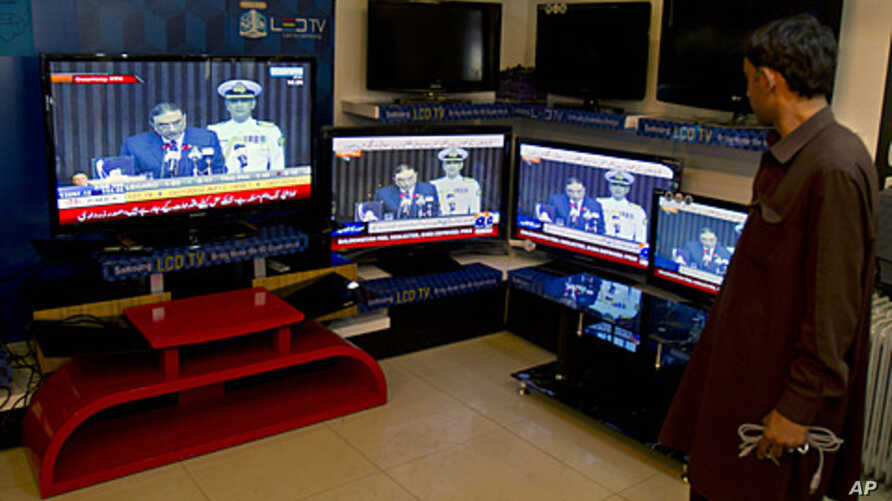 A Pakistani man listens to President Asif Ali Zardari's speech to joint session of parliament, on televisions at an electronics shop in Islamabad, March 17, 2012.