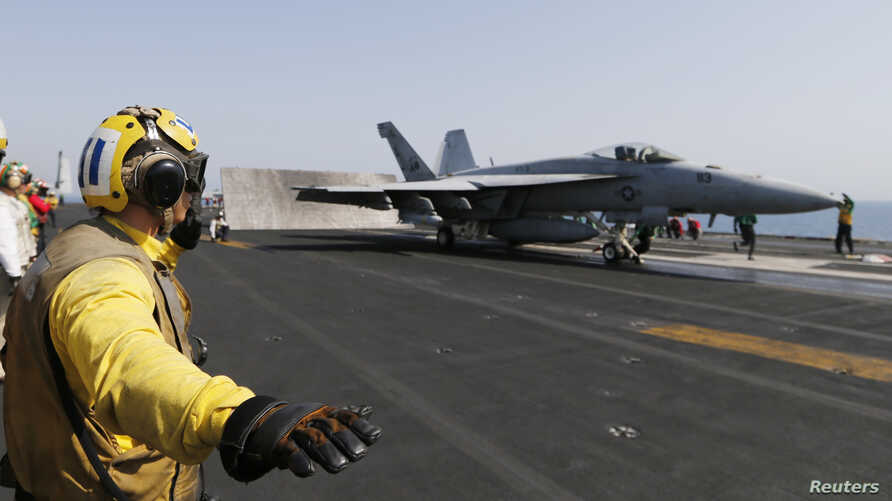 A flight deck crew member is seen giving an 'all clear' before a F/A-18C Hornet takes off from the aircraft carrier USS George H.W. Bush in the Persian Gulf August 12, 2014.