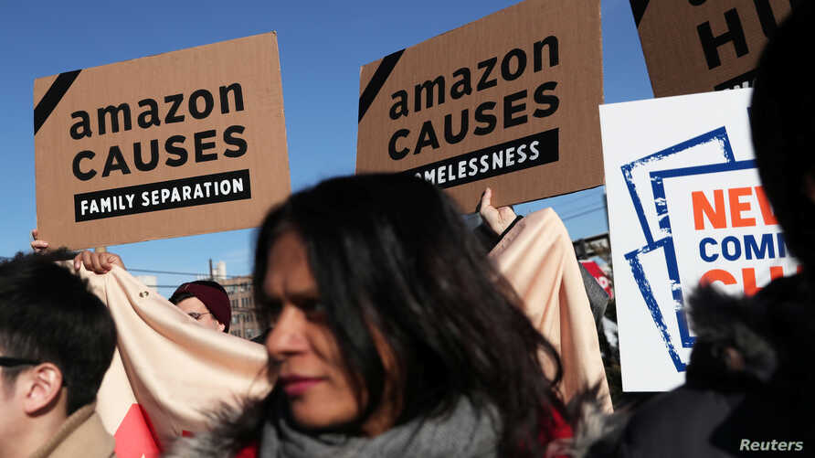 Demonstrators hold signs during a protest against Amazon in the Long Island City section of the Queens borough of New York, Feb. 14, 2019.