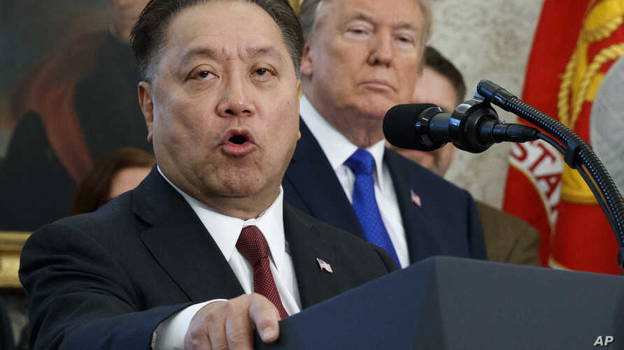 FILE - Broadcom CEO Hock Tan speaks while U.S. President Donald Trump listens, in background, during an event at the White House in Washington, Nov. 2, 2017.