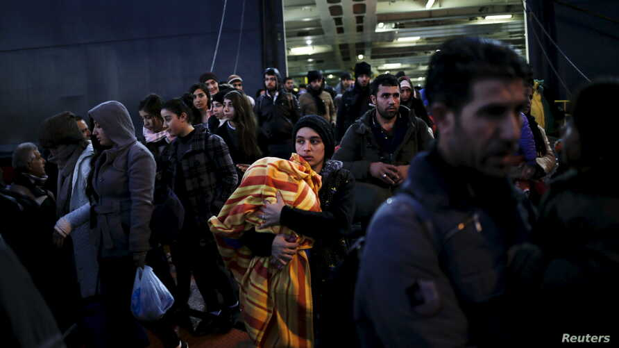 Refugees and migrants arrive aboard the passenger ferry Nissos Rodos at the port of Piraeus, near Athens, Greece, Jan. 13, 2016.