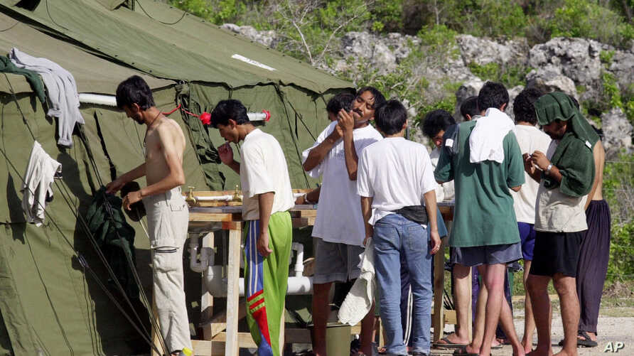 FILE - Men shave, brush their teeth and prepare for the day at a refugee camp on the Island of Nauru, Sept. 21, 2001.