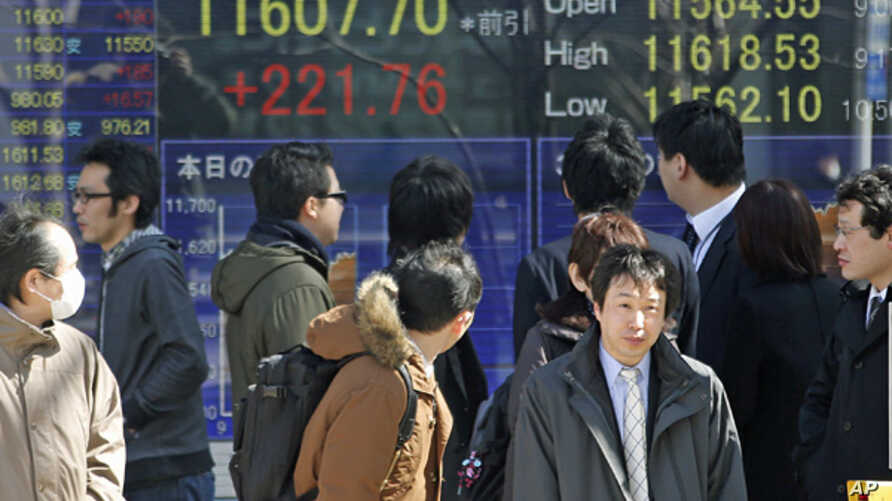 People look at an electronic stock board of a securities firm in Tokyo, Feb. 25, 2013.