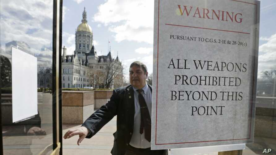 A Capitol security officer enters a revolving door at the legislative office building, with a sign warning not to bring weapons on to the grounds at the Capitol in Hartford, Conn., April 3, 2013.