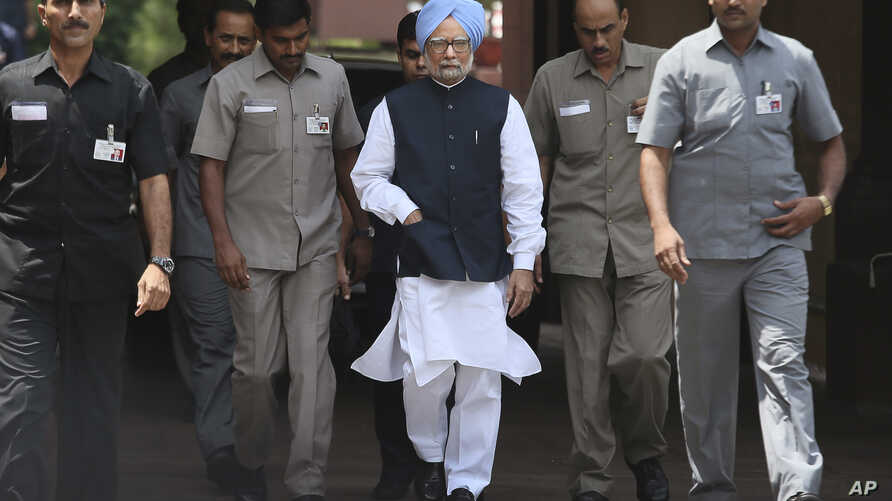Indian PM Manmohan Singh, center, arrives to make a statement to the media after he was shouted down by opposition politicians in the lower house of Parliament, in New Delhi, India, August 27, 2012.
