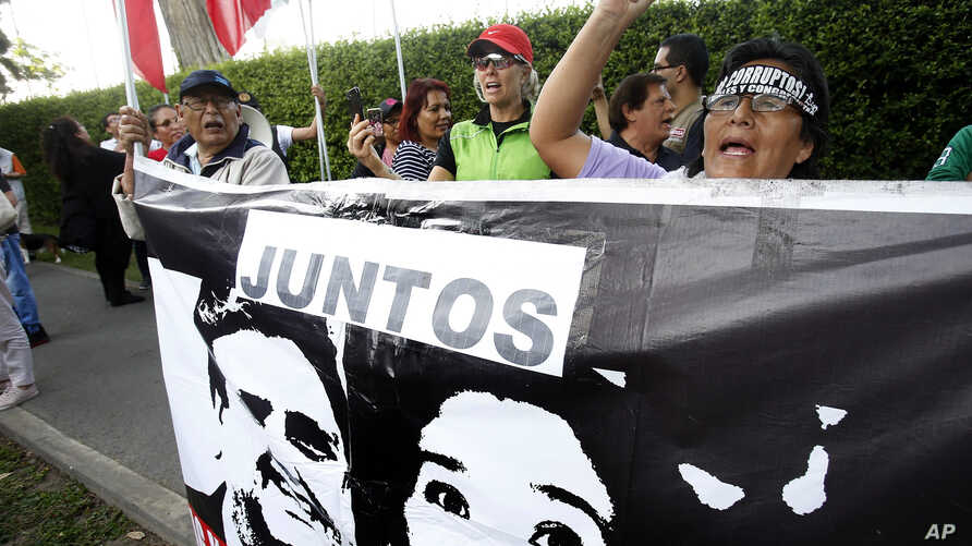 A woman shouts slogans against Peru's former president Alan Garcia outside the residence of Uruguay's ambassador to Peru, behind a sign showing an image of Garcia and Keiko Fujimori, in Lima, Peru, Nov. 18, 2018.