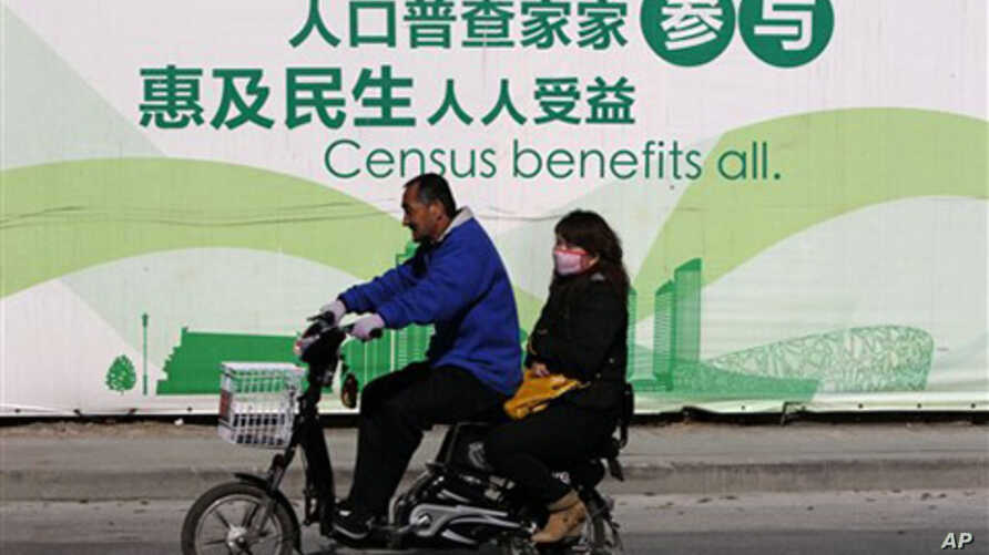 A man and woman ride an electric bicycle past a publicity board China's census in Beijing, 1 Nov. 2010. China kicked off its once-a-decade census on Monday, a whirlwind 10-day head count.