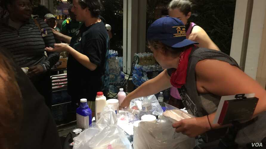 Volunteers hand out donated water bottles and antidotes to tear gas (masks, milk of magnesia, and vinegar) as protestors prepare to leave Romare Bearden Park and march through Charlotte, North Carolina, Sept. 24, 2016.