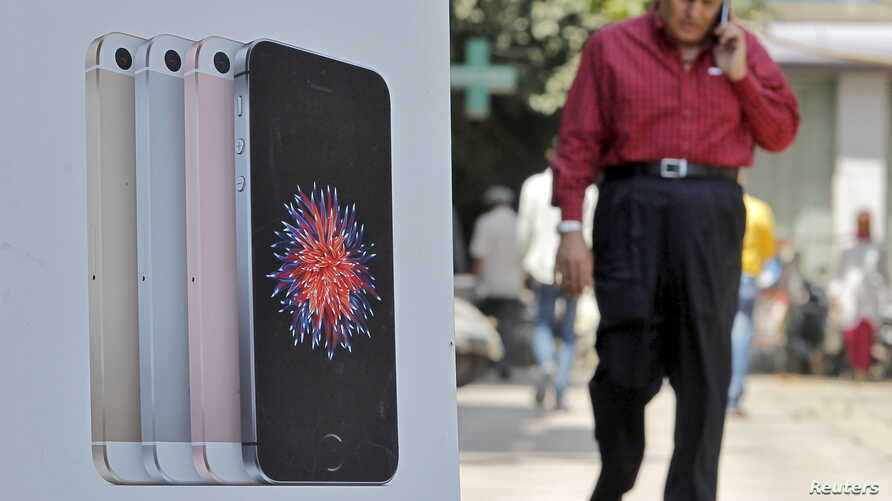 A man speaks on his mobile phone as he walks past an Apple iPhone SE advertisement billboard in a street in New Delhi, India, April 25, 2016.