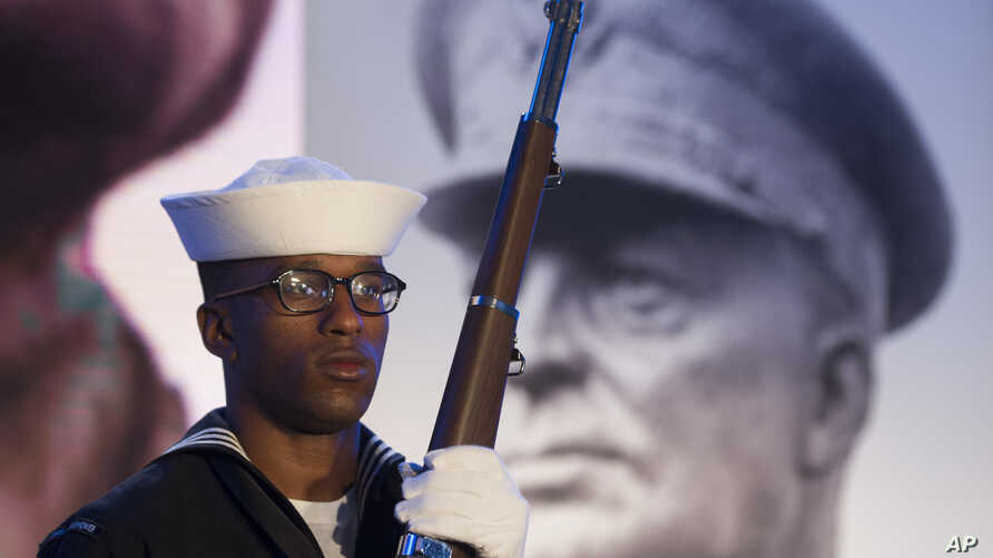FILE - A Navy sailor and member of an honor guard stands in front of a photograph of Gen. Dwight D. Eisenhower during the groundbreaking at the site of the Dwight D. Eisenhower Memorial, in Washington,  Nov. 2, 2017.