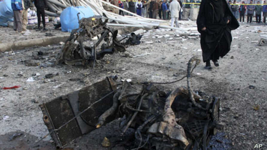 A woman walks at the site of a bomb attack that occurred in Sadr city in northeastern Baghdad January 24, 2012.