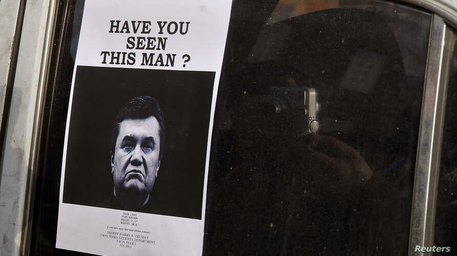 """A man takes photos of a """"Wanted"""" notice, of fugitive Ukrainian President Victor Yanukovich, plastered on the window of a car used as barricade near Kiev's Independent Square February 24, 2014"""