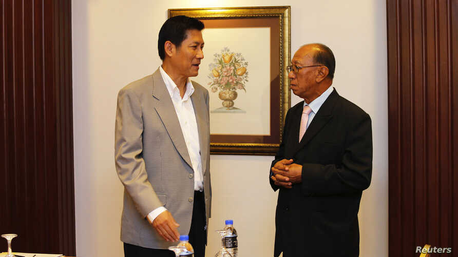 Secretary-General of Thailand's National Security Council Paradorn Pattanathabutr (L) speaks to Chairman of the Advisory Council for Peace Building in the Southern Border Provinces Aziz Benhawan, before a meeting ahead of talks with Thailand's Nation