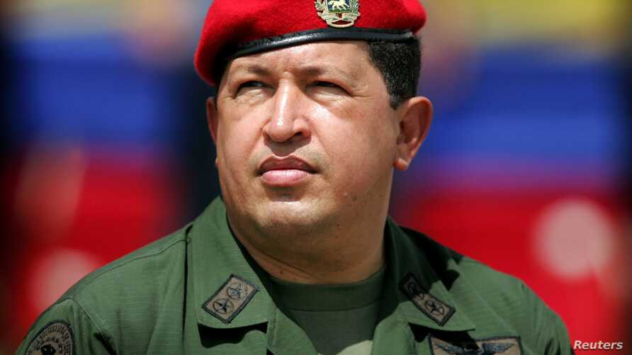 FILE - Venezuelan President Hugo Chavez wears an army uniform and the red beret of his parachute regiment while he attends a military parade in Caracas, April 13, 2005.
