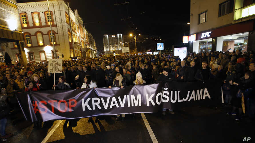 People hold a banner that reads: ''Stop to bloody shirts'' during a protest in Belgrade, Serbia, Dec. 8, 2018. Thousands of people marched in Serbia against the autocratic rule of President Aleksandar Vucic and his government.