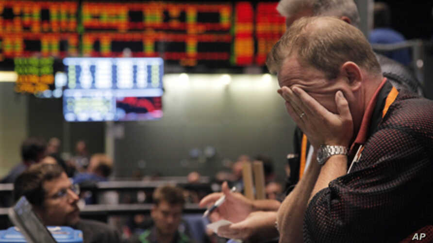 Trader Andrew Stavros reacts after the close of trading in the NASDAQ, 100 Index pit, on the floor of The CME Group Monday, Aug. 8, 2011, in Chicago.