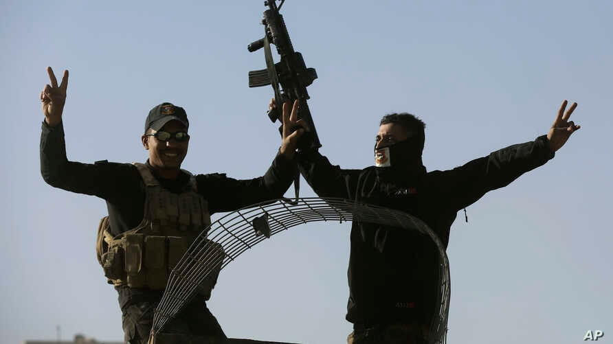 Iraqi special forces soldiers flash victory signs, as they arrive to relieve soldiers returning from the battlefield, in the Al-Samah front line neighborhood, in Mosul, Iraq, Wednesday, Nov. 23, 2016. An airstrike by the U.S.-led coalition on Wednesd