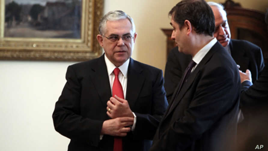 Greek Prime Minister Lucas Papademos (L) speaks with newly appointed Finance minister Philippos Sachinidis in Athens on March 21, 2012.