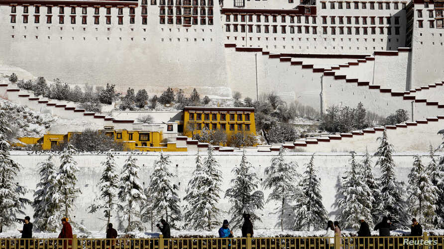 People walk past snow-covered trees outside the Potala Palace in Lhasa, Tibet Autonomous Region, China, Dec. 19, 2018.