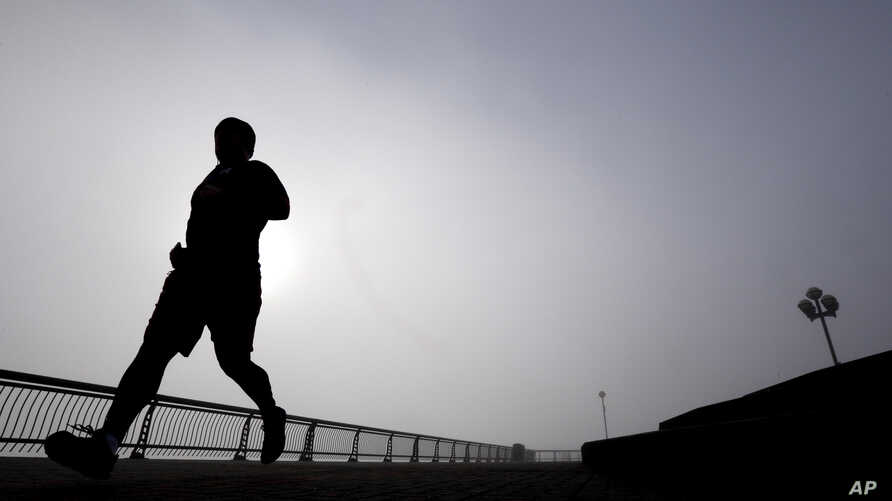 FILE - A man jogs at Pier A Park in Hoboken, New Jersey, Jan. 15, 2014. Atherosclerosis, or calcium deposits, in the cardiac arteries of young people have been found to dramatically shorten life expectancy, a new study found.