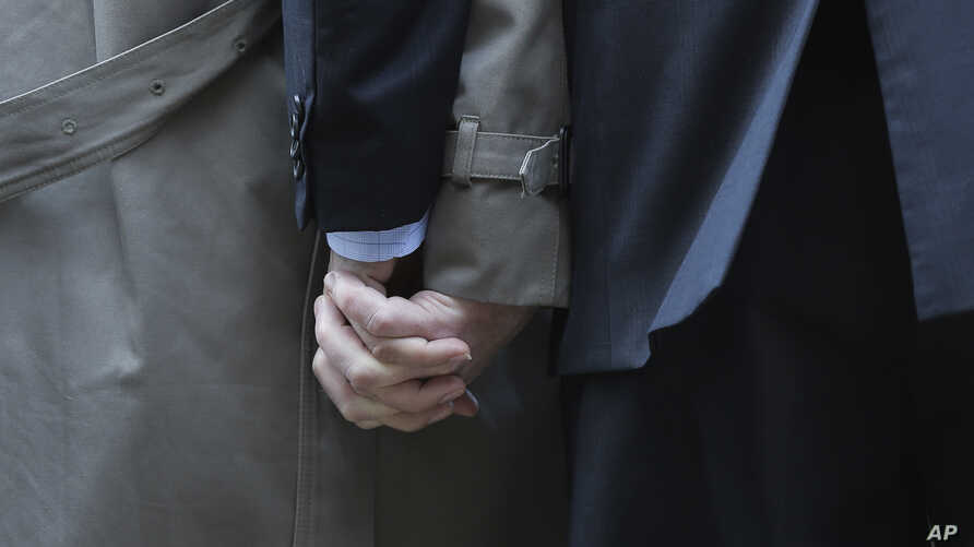Mark Phariss (L) clutches the hand of partner Victor Holmes as they talk to the media outside the U.S. Federal Courthouse in San Antonio, Texas, Feb. 12, 2014.