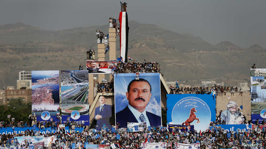 FILE - Supporters of Yemen's former President Ali Abdullah Saleh (pictured in poster) climb pillars of the Unknown Soldier Monument during a rally to mark the 35th anniversary of the establishment of the General People's Congress party which is led b