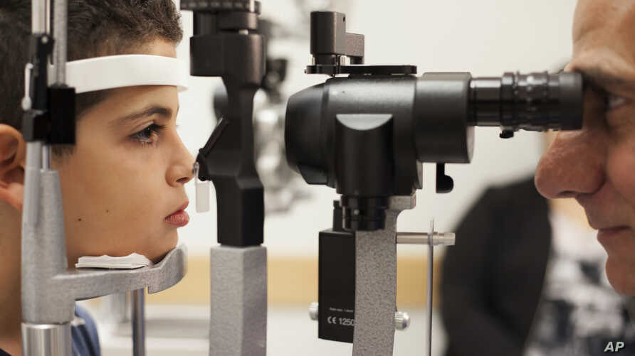 FILE - Dr. Albert Maguire checks the eyes of Misa Kaabali, 8, at Children's Hospital of Philadelphia, Oct. 4, 2017. Misa was 4 when he received his gene therapy treatment. On Dec. 19, 2017, the Food and Drug Administration approved therapy that impro