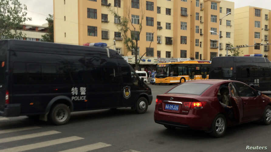 Police vehicles of the Special Weapons and Tactics (SWAT) team are seen after a blast occurred, on a road in Urumqi, Xinjiang Uighur Autonomous Region, May 22, 2014.