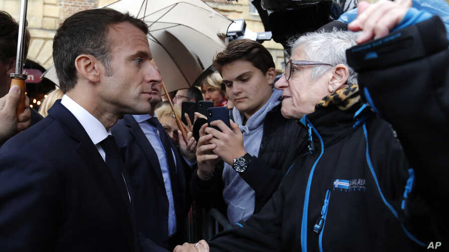 French President Emmanuel Macron argues with a resident as he arrives for a meeting at the city hall in Charleville-Mezieres, eastern France, Nov. 7, 2018 as part of a World War One commemoration tour.