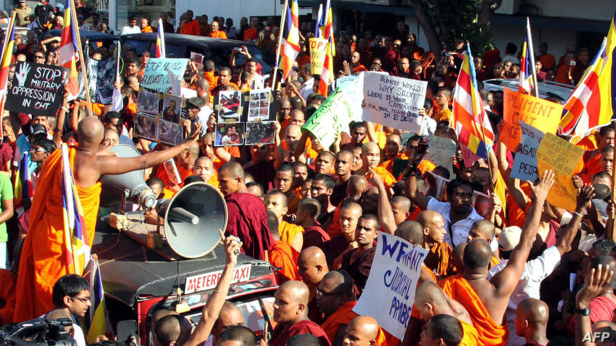 Sri Lankan Buddhist monks shout slogans and hold placards as they stage a protest rally outside the Bangladesh High Commission in Colombo on October 4, 2012.