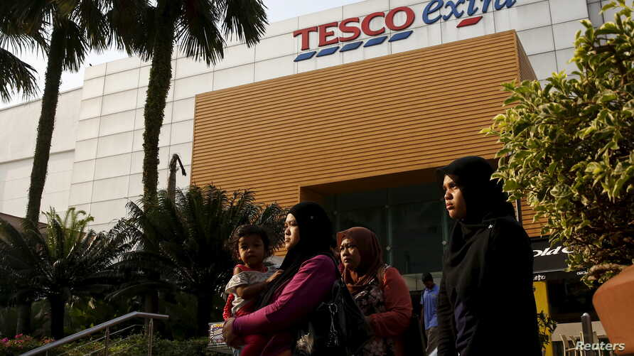 FILE - Shoppers are seen outside a Tesco Extra store in Kuala Lumpur, Malaysia, July 6, 2015.