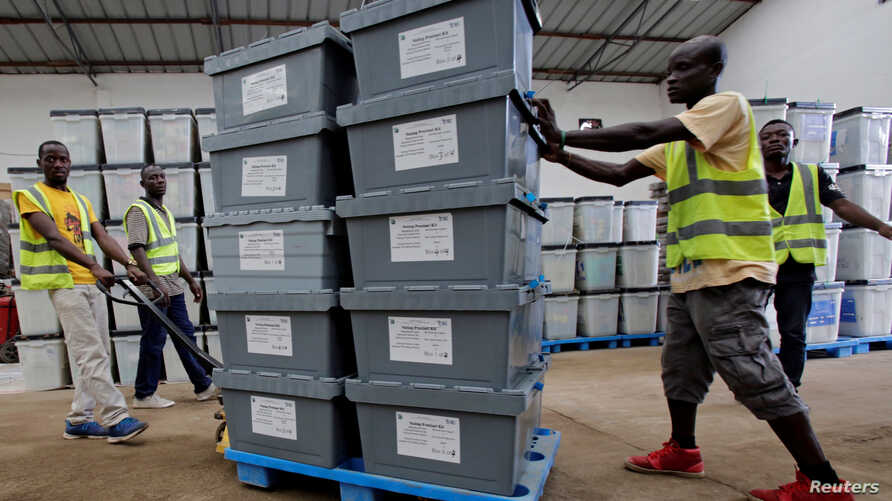 Election workers move boxes of voting materials at the National Electoral Commission headquarters in Monrovia, Oct. 9, 2017.
