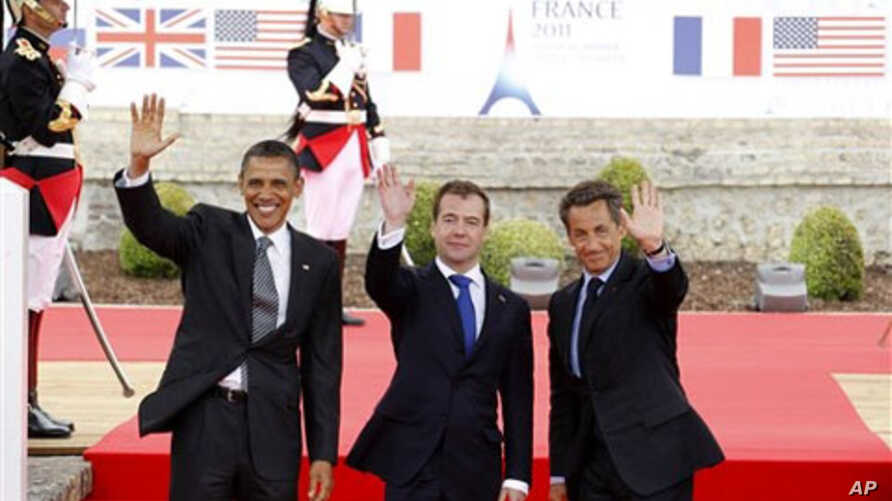 From left, US President Barack Obama, Russian President Dmitry Medvedev and French President Nicolas Sarkozy wave as they arrive for a lunch meeting at the Villa le Cercle during the G8 summit in Deauville, France, Thursday, May 26, 2011. G8 leaders,