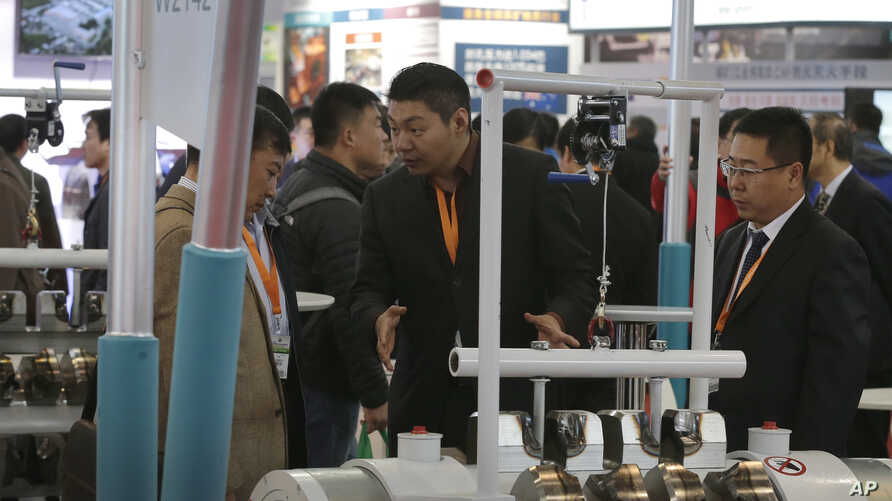 An exhibitor, center, talks to a visitor about his company's machine at the China Coal & Mining Expo in Beijing, China, Oct. 30, 2015. World Bank experts say economic growth will slow further in China this year.
