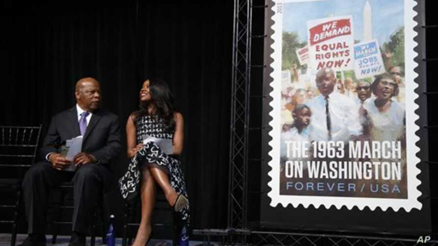 Actress Gabrielle Union and Congressman John Lewis sit on stage at the Newseum in Washington, D.C., at the unveiling of a U.S. Postal Service stamp commemorating the 50th anniversary of the March on Washington, Aug. 23, 2013.