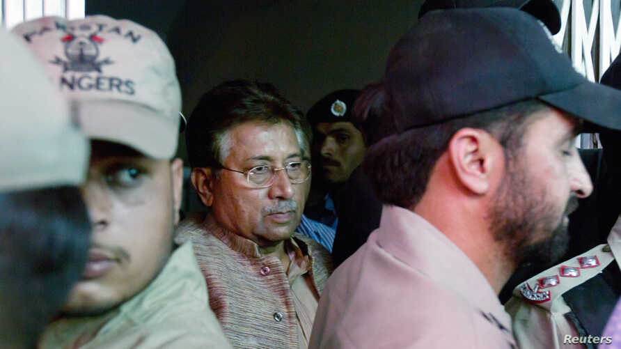 FILE - Pakistan's former president and head of the All Pakistan Muslim League (APML) political party Pervez Musharraf (C) is escorted by security officials as he leaves an anti-terrorism court in Islamabad.