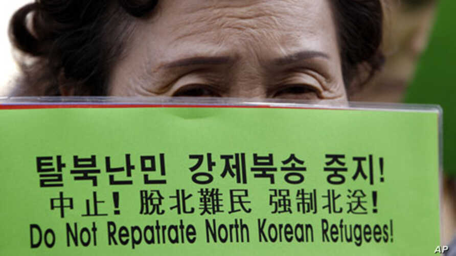 A North Korean defector holds a banner during a rally for North Korean refugees who were repatriated by the Chinese government, in front of the Chinese Embassy in Seoul, South Korea. (2011 File)